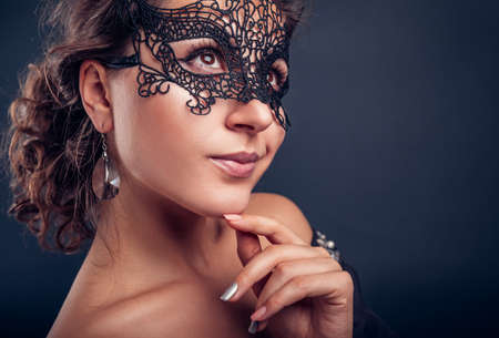 Photo pour New year masquerade party. Beautiful young woman wearing black lace carnival mask and jewellery. Fashionable look. - image libre de droit