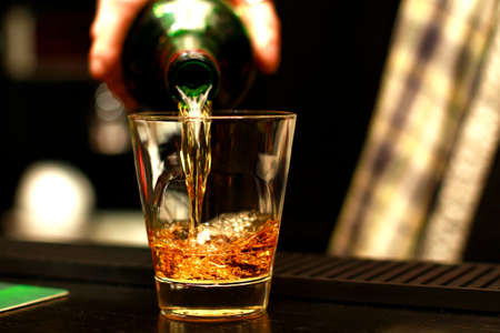Photo pour A glass cup in which hand of a bartender in a kilt pours from a bottle of alcohol (whiskey, brandy, scotch, liquor, vodka, cognac), a glass with a close standing on a wooden table - image libre de droit