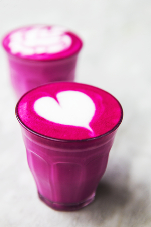 Two Beetroot super latte on marble background. It is love symbol in front