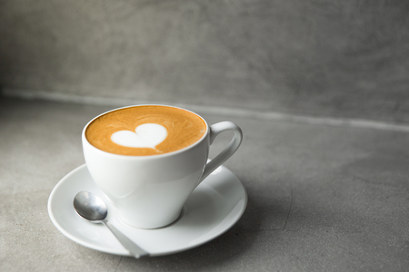 Foto de White cup of tasty cappuccino with love art latte. Valentine's day concept. Concrete grey backdrop. Copy space - Imagen libre de derechos