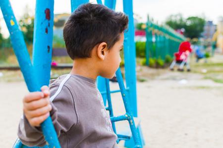 dark-haired boy swinging on a swing