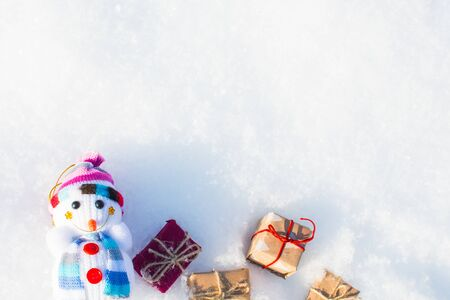 Photo for funny toy snowman with gifts in a snowdrift with a copy of space - Royalty Free Image