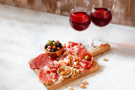 Meat plate, cured jamon, prosciutto, salami served with wine, nuts and olives copy spaceの写真素材