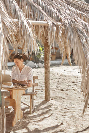 Young woman using laptop computer on a beach. Freelance work concept. Pretty young woman using laptop in cafe on tropical beach in outdoor cafe. Work and travel