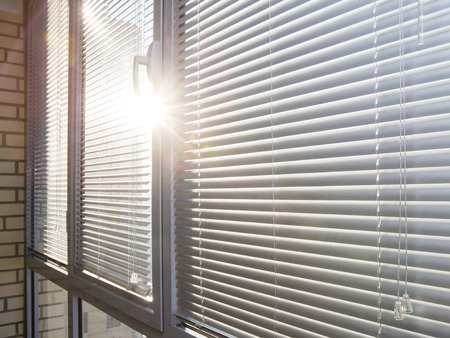Photo for Closed aluminum window on sunny day with horizontal plastic blinds - Royalty Free Image