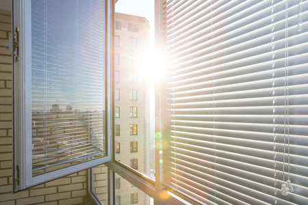Photo pour Opened window on sunny day with horizontal plastic blinds - image libre de droit