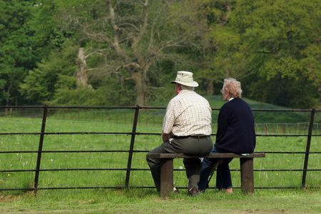 Elderly couple sitting together on a bench in front of a fence, gazing at a rural view .の写真素材