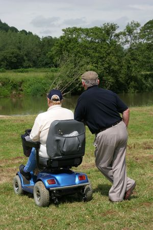 Two elderly men, one sitting on an electric  mobility scooter and one standing with both looking at a river bank in rural countryside. Rear view.