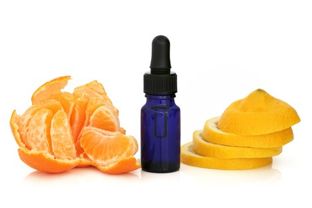 Tangerine  peeled and lemon slices with an aromatherapy blue glass essential oil dropper bottle. Isolated over white background.