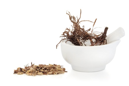 Foto für Valerian herb root in a porcelain mortar with pestle with a chopped pile to one side, isolated over white background. Valeriana. Modern day equivalent is valium and diazipam.   - Lizenzfreies Bild