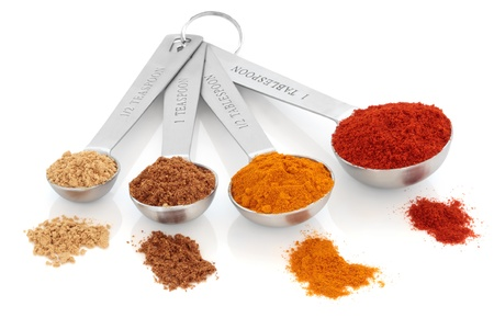 Spice selection of paprika, turmeric, chinese five spice and  ginger in stainless steel measuring spoons, and loose, over white background. Right to left. Selective focus.