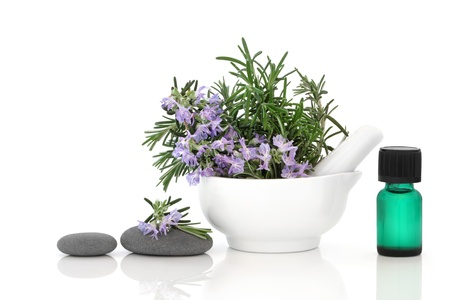 Rosemary herb flower sprigs in a porcelain mortar with pestle, spa stones, and aromatherapy essential oil bottle, isolated over white background.