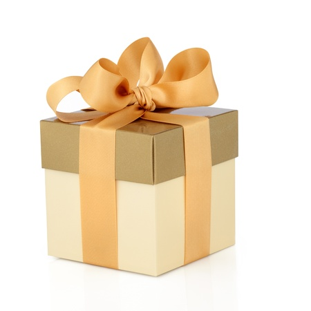 Gift box in gold duo tone with golden satin ribbon and bow isolated over white background.