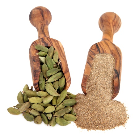 Cardamom pods and ground powder spice in olive wood scoops over white background