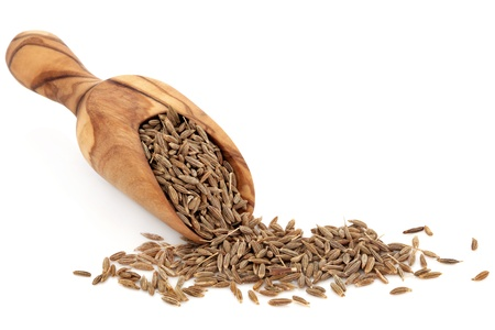 Caraway seed in an olive wood scoop and scattered over white background