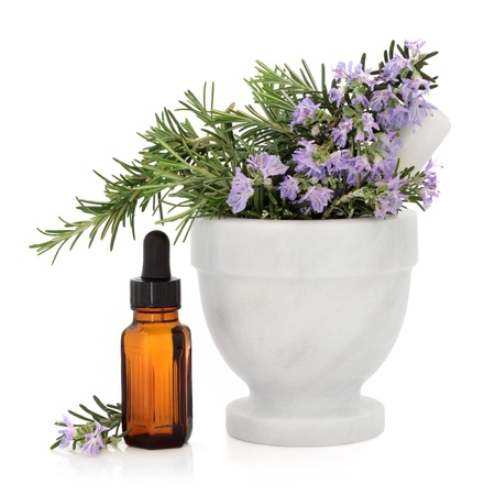 Rosemary herb in a marble mortar with pestle with aromatherapy essential oil bottle over white background