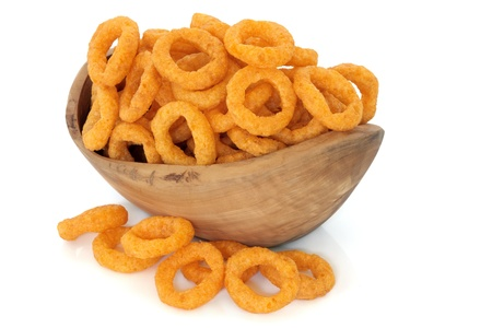 Onion ring crisps in an olive wood bowl and loose over white background