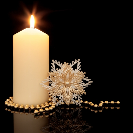 Christmas decoration of gold bead chain, snowflake sparkling bauble and lit candle with holder over black background