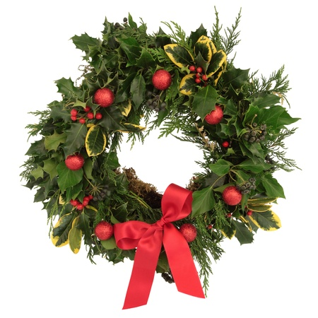 Christmas decorative wreath of holly, ivy, cedar cypress leaf sprigs and red bauble decorations with bow over white background