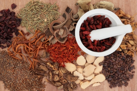 Traditional chinese herbal medicine selection with mortar and pestle over papyrus background
