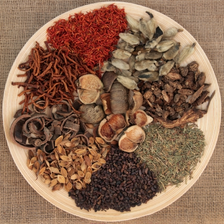 Traditional chinese herbal medicine selection on a wooden bowl over hessian background