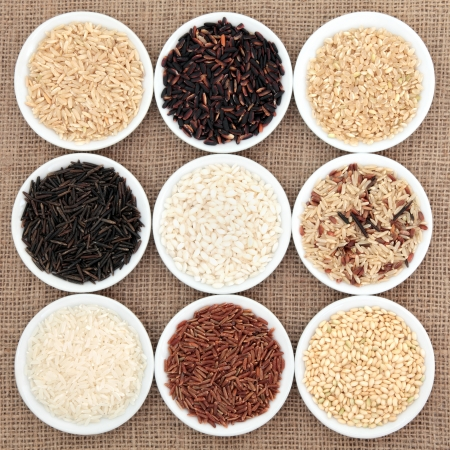 Rice grain varieties in white round porcelain bowls over hessian background