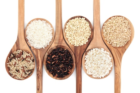Rice varieties in olive wood spoons over white background  Wild, white, american, sweet, risotto and brown left to right