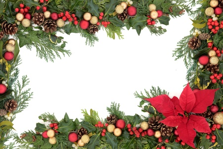 Christmas floral border with red poinsettia flower, baubles, holly, mistletoe and winter greenery over white background