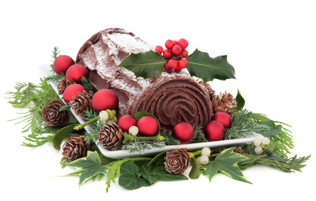 Christmas chocolate yule log cake with red baubles and holly over white background