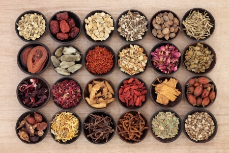 Large chinese herbal medicine selection in wooden bowls over papyrus background