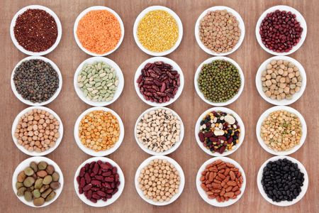 Large dried pulses selection in white porcelain dishes over papyrus background