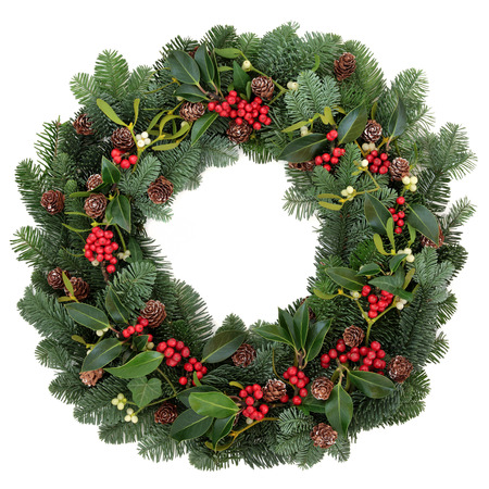 Winter and christmas floral wreath with holly, ivy, mistletoe and spruce fir over white background