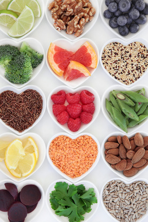 Foto de Healthy super food selection in heart shaped porcelain dishes over white background. - Imagen libre de derechos
