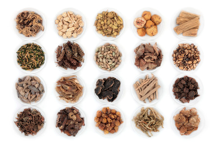 Large chinese herbal medicine selection in china bowls over white background.
