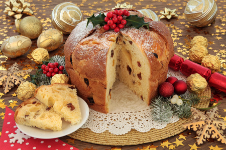 Italian panettone christmas cake and slice with red and gold bauble decorations, holly and winter flora over oak background with stars.