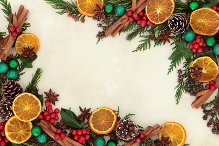 Christmas background border with dried fruit and spices, green bauble decorations, holly and winter greenery over old parchment paper.