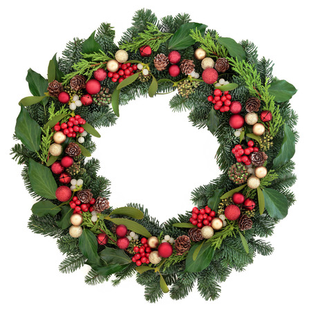 Christmas wreath with red bauble decorations, holly, ivy, mistletoe and winter greenery over white background.
