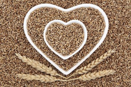 Wheat grain food in heart shaped bowls with sheaths forming an abstract background.