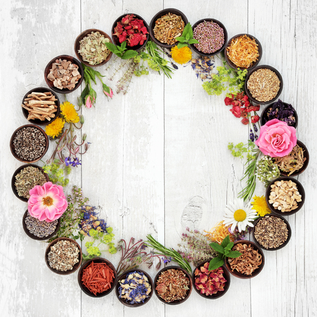 Photo pour Natural flower and herb selection used in herbal medicine in bowls and loose forming a circle over distressed wooden background. - image libre de droit