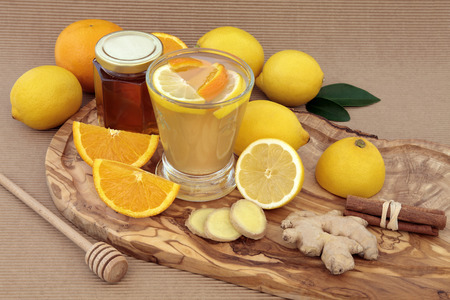 Vitamin c health remedy relief drink for cold and flu, with lemon and orange fruit, ginger and cinnamon spice and honey on an olive wood board.