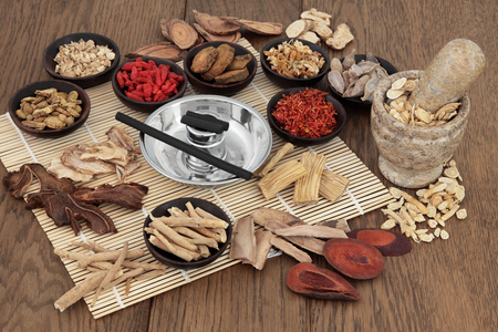 Photo pour Moxa sticks and chinese herbs used in traditional herbal medicine with mortar and pestle over bamboo and oak background. - image libre de droit