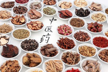 Traditional chinese medicinal herb ingredients with calligraphy on rice paper. Translation reads as chinese herbal medicine.