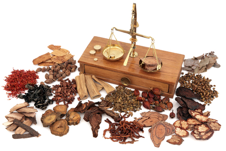 Foto de Chinese herb ingredients used in traditional herbal medicine with old brass scales over white background. - Imagen libre de derechos