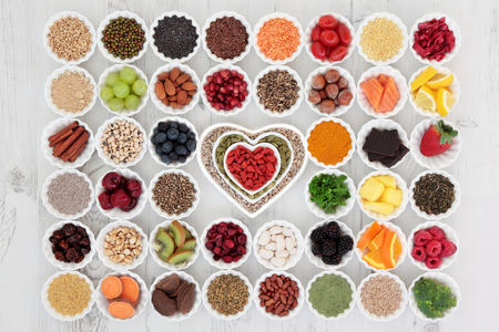 Foto für Large superfood selection in porcelain crinkle bowls and heart shaped dishes over distressed wooden background. High in vitamins and antioxidants. - Lizenzfreies Bild