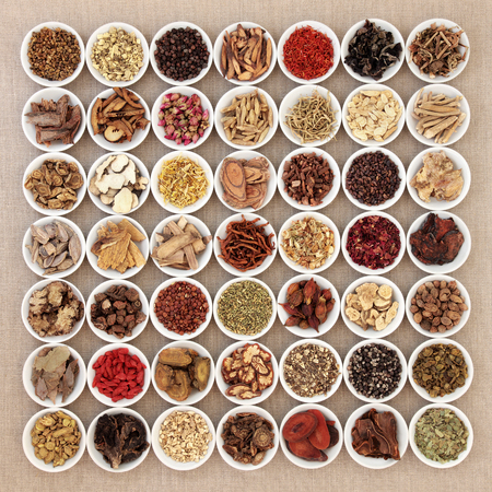 Foto de Traditional chinese herbal medicine ingredients in white china bowls over hessian background. - Imagen libre de derechos