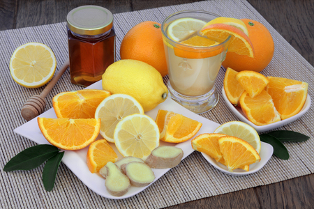 Natural flu and cold remedy drink in a glass with orange and lemon fruit, fresh ginger and honey on bamboo  over oak background.