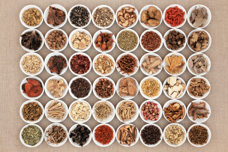 Photo pour Chinese herbal medicine selection in white china bowls over hessian background. - image libre de droit