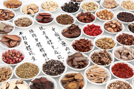 Foto de Chinese herbal medicine ingredients with calligraphy on rice paper. Translation reads as chinese herbal medicine as increasing the bodys ability to maintain body and spirit health and balance energy. - Imagen libre de derechos