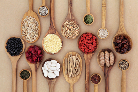 Dried super health food selection in wooden spoons over natural paper background. High in antioxidants, minerals, vitamins and dietary fiber.