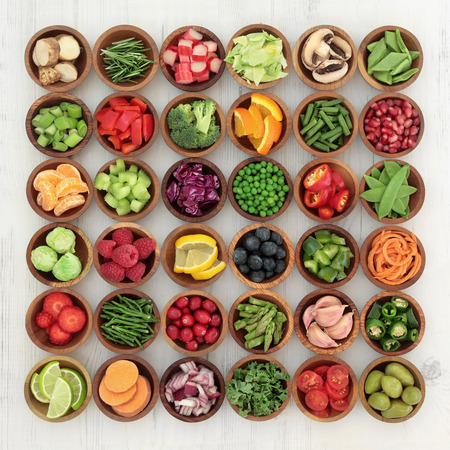 Paleolithic super health food of fruit and vegetables in wooden bowls over distressed white wood background. High in vitamins, antioxidants, minerals and anthocyanins.